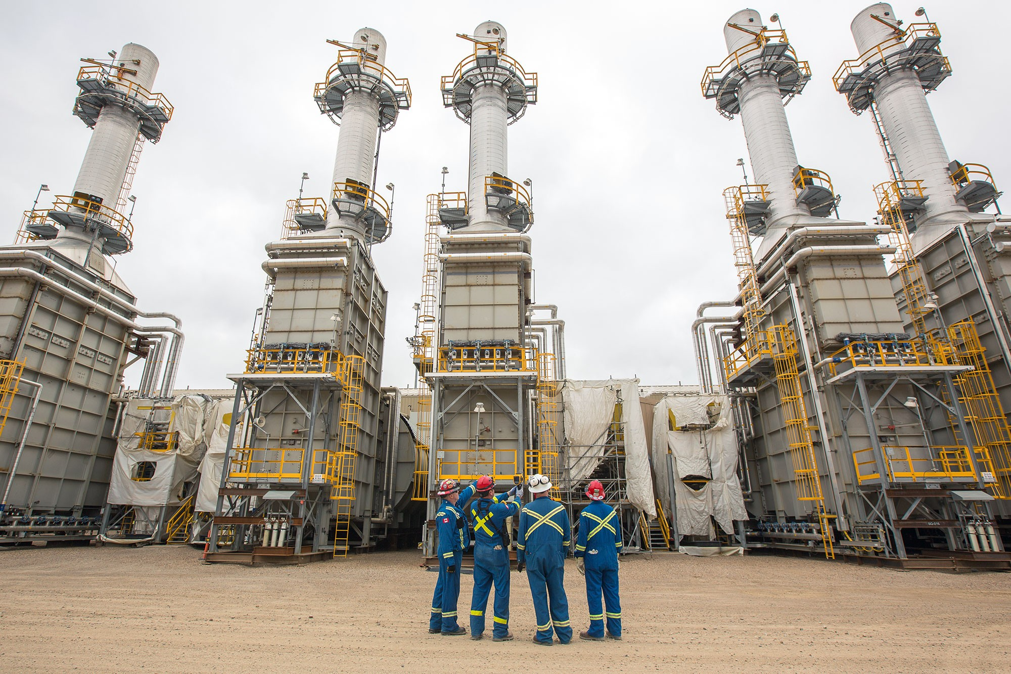 4 workers wearing protective clothing with towers in background
